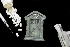 Drug Abuse. Headstone on black background with handgun, pills and syringe waring of dangers of drug abuse Stock Photo