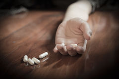 Drug abuse concept, passive hand on floor with spilled pills Stock Photo