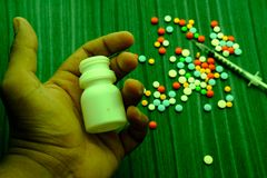 Drug abuse concept - passive hand on table, pills and injection Royalty Free Stock Photos