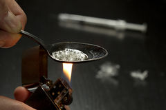 Drug addict cooking heroin using lighter Royalty Free Stock Photos