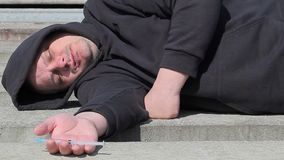 Drug addict man sleeping with syringe in hand at outdoor stock video