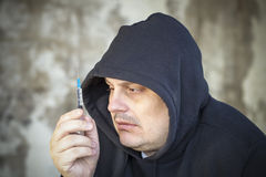 Drug addict men looks at the syringe Royalty Free Stock Photo