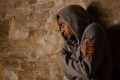 Drug addict posing near brick wall. Addicted, breaking, pain, depression, drama, illness, dependence Ill person hugging himself Royalty Free Stock Photo