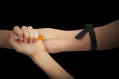 Drug addict pricking in the arm a drug with the syringe Royalty Free Stock Photography