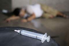 Drug addict and syringe on floor. Unconscious drug addict laying on floor with syringe in the foreground royalty free stock image