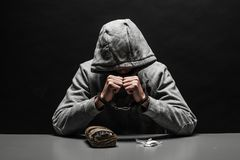The drug addict was arrested for drug use at the table. suffering from addiction on a dark black background. The drug addict was arrested for drug use at the royalty free stock photo