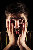 Drug addicted. Man being high after sniffing cocaine and holding his face in his hands. Chiaroscuro photography Stock Photos
