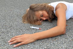 Drug-addicted Teenager wirh syringe lying on a street Stock Images