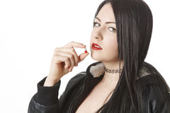 Drug addicted woman. Young twenty year old woman taking a red and white pill Stock Image