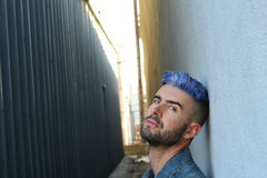 Drug addicted young rebel man with blue dyed hair sitting on suspicious dark alley way. Drug addicted young rebel man with blue died hair sitting on suspicious Stock Images