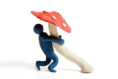 Drug addiction. Plasticine man embraces a mushroom stock image