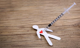 Drug Addiction Concept. Paper man with heart  and syringe. On wooden background Royalty Free Stock Photos