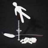 Drug Addiction Concept. Paper man with syringe and pills. Over black background Stock Photography
