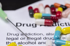 Drug addiction. Pills spilled on top of report about drug addiction with syringe on the side stock images