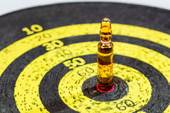 Drug Ampoule on Old Yellow Target Board. Therapy concept: drug ampule on old yellow target board. Shallow depth of field Stock Image