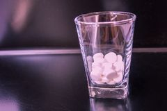 Drug from binge. White tablets in a vodka glass. A shiny black bar, the background is blurred. Violet tinting royalty free stock photos