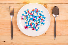 Drug capsule on white  plate Royalty Free Stock Image