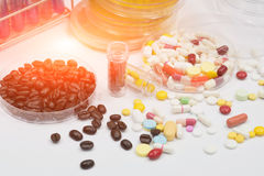 Drug and coffee test in laboratory,pathogen culture for drug and. Pharmaceutical medicament, cure in container for health and fresh roasted coffee beans in plate Stock Image