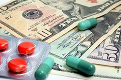 Drug Costs. Photo of Pills With Money. Drug Cost Concept Stock Photos
