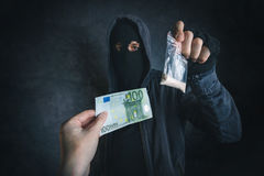 Drug dealer offering narcotic substance to addict on the street. Unrecognizable hooded criminal selling drugs in dark alley for euro banknotes Stock Photo