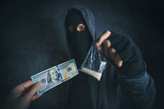 Drug dealer offering narcotic substance to addict on the street. Unrecognizable hooded criminal selling drugs in dark alley for dollar baknotes royalty free stock photo
