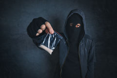 Drug dealer offering narcotic substance to addict on the street. Unrecognizable hooded criminal selling drugs in dark alley, addicted person point of view Stock Photos
