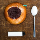 Drug dependence on the sweet. Still life with bun with jam, game, spoon and lighter Royalty Free Stock Photos