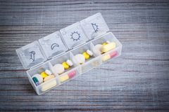 Daily drug dose. Pills organized in a pill box royalty free stock image