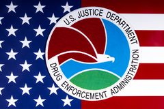 Drug Enforcement Administration Seal and US Flag. LONDON, UK - MARCH 27TH 2018: The seal or symbol of the Drug Enforcement Administration of the US Justice Stock Images
