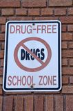 Drug Free School Zone. A drug free school zone on the front wall of an American city school. The same sign in Spanish is on a nearby wall royalty free stock photos