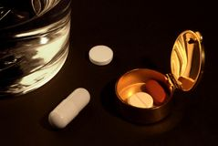 Drug ingestion. Pill box with tablets and a glass of water on a dark background stock photo