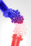 Drug Interaction. Pharmaceutical concept showing drug interaction between red and blue pill bottles stock photos