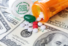 Drug and medical costs - healthcare. Pills spilling out of a medicine bottle onto hundred dollar bills, a concept showing the cost of healthcare Royalty Free Stock Images