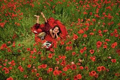 Drug, narcotics, opium, woman with typewriter, camera, book. Drug and narcotics woman in poppy flower royalty free stock image