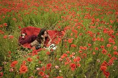 Drug, narcotics, opium, woman with typewriter, camera, book. Opium poppy, agile business, ecology. Poppy, Remembrance or Anzac Day. Woman writer in poppy royalty free stock image