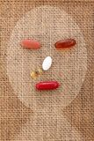 Drug pill on the burlap human sick face form Royalty Free Stock Photography