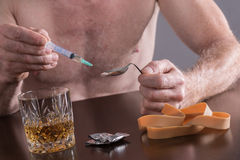 Drug preparation. Drug addict preparing a dose of heroin Stock Images