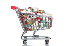 Drug shopping. A shopping cart full of pills, capsules and medicine - isolated on white Royalty Free Stock Photo