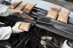 Drug smuggled in a cars engine compartment. Hidden drugs in a vehicle compartment Royalty Free Stock Image