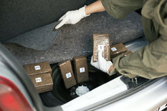 Drug smuggling. Drug packages smuggled in a vehicle's trunk Royalty Free Stock Image
