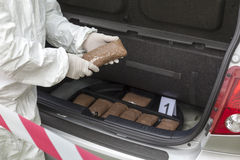 Drug smuggling. Drug bundles smuggled in a car trunk Royalty Free Stock Image