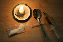 Drug syringe and cooked heroin on spoon. Cocaine in the bag, sca. Ttered. Candle burns. Evening Royalty Free Stock Image