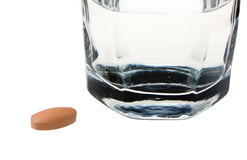 Drug tablet in front of glass of water. Glass of water and drug tablet on white background Royalty Free Stock Image