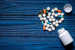 Drug therapy. Pills and pill bottle on blue wooden table background top view copyspace royalty free stock images