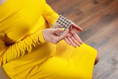 Woman waiting for a child and holding pills. Drug therapy during pregnancy concept. Faceless image, top view of pregnant woman squeezing a tablet from a blister royalty free stock photo