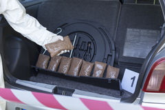 Drug trafficking. Drug bundles smuggled in a car trunk Royalty Free Stock Photography