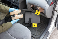 Drug trafficking. Policeman holding drug packages discovered in secret compartment of the car Stock Photography