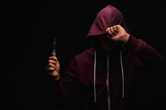 A drug user in a purple sweatshirt with a hood on his head suffers from drug addiction on a dark black background. Royalty Free Stock Photo
