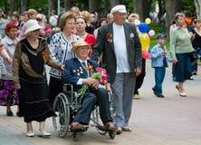 Druga Wojna Światowa weteran w wózku inwalidzkim i towarzyszący krewnymi na zwycięstwo dnia świętowaniu na alei bohaterzy w Volgo obrazy royalty free