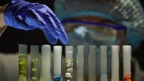 Drugfabrikant die chemische agens toevoegen in buizen met multicolored vloeistoffen stock videobeelden